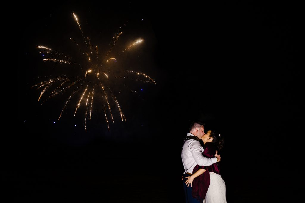 newlyweds kissing under fireworks derby wedding photography by emma and rich