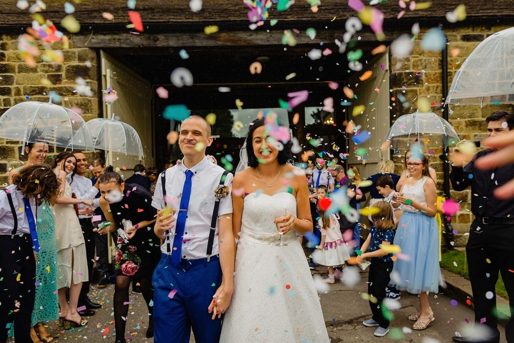 bride and groom under confetti cloud outside east riddlesden hall