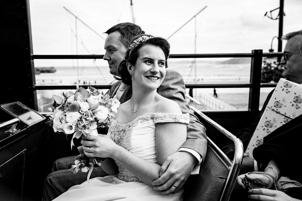 bride and groom riding an open top bus to their betton farm wedding
